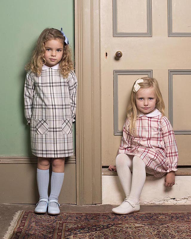 Photo of two little girls in similar dresses, one standing and one sitting on a doorstep.