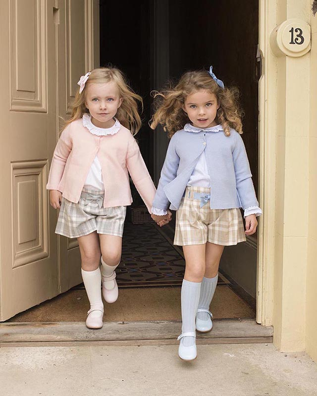 Two little girls wearing matching clothes stepping out hand-in-hand through a large old doorway