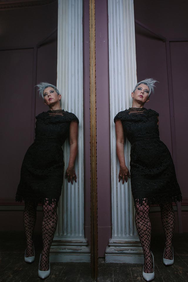 A woman wearing a black dress and leaning against a white wooden column, the whole reflected in a large mirror.