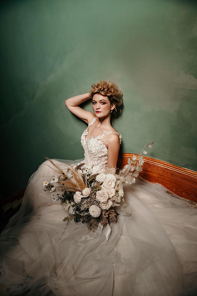 Woman reclining in bridal dress holding bouquet of dried flowers
