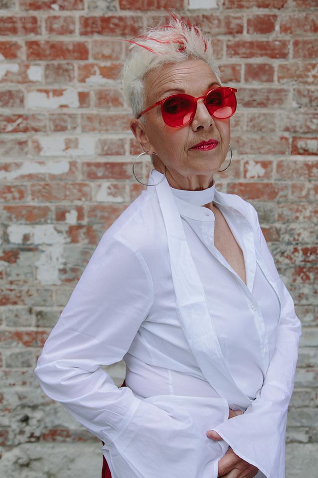 Older woman with short, spikey white hair and large red glasses wearing a white blouse, behind her a plain brick wall.