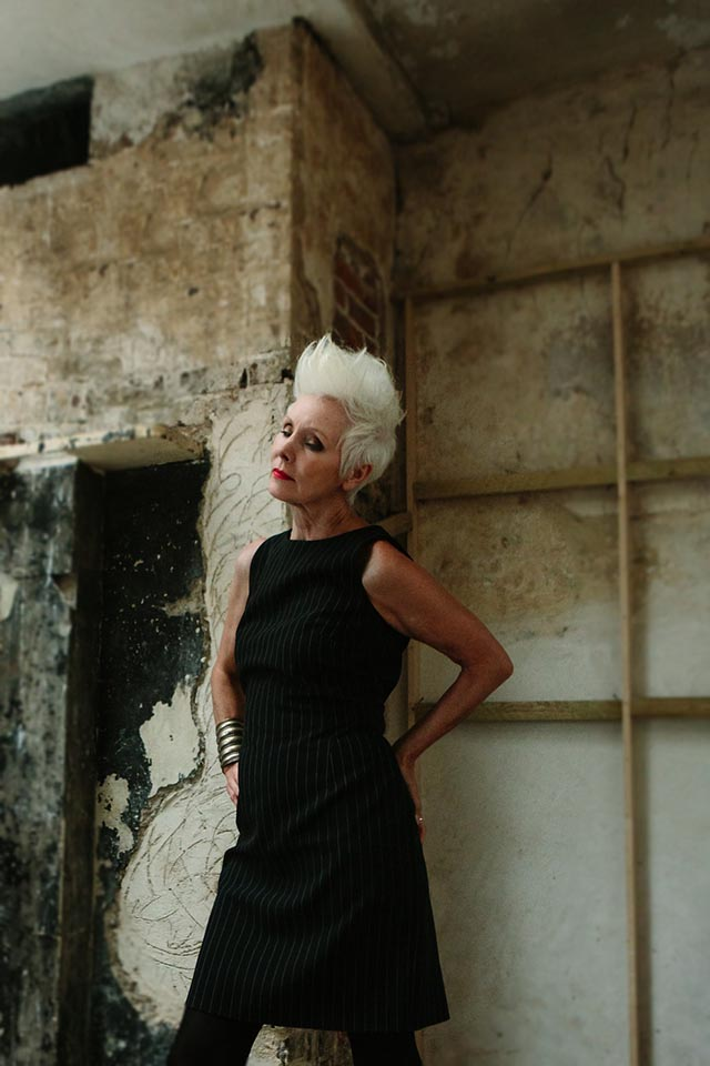 Woman with white spiky hair wearing a black pinstriped dress and standing in a derelict room.
