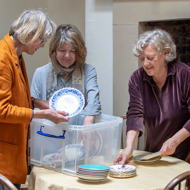 Photo of three women examining antique tableware