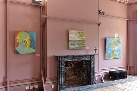 Photo of dining room south wall showing fireplace and three paintings hanging