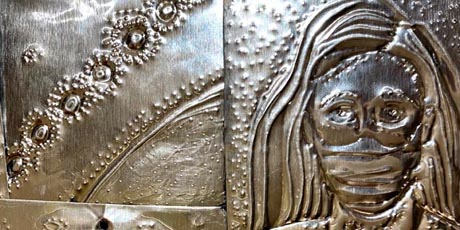 Shiny metal pieces embossed with designs representing coronavirus and a health worker wearing a mask