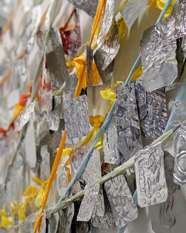 A vertical surface festooned with shiny metal tags embossed with various designs, each tied in place by a network of coloured ribbons.