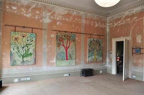 Photo of north wall of the drawing room, showing three large paintings hanging from a steel tube.