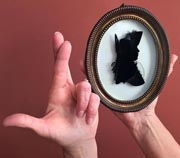 Photo of two hands, one with fingers crossed, the other holding a framed silhouette portrait