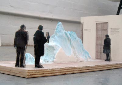 A model of the 'Iceberg' installation by Mariele Neudecker, showing several flat cut-out figures arranged around a representation of the iceberg on a plywood base.