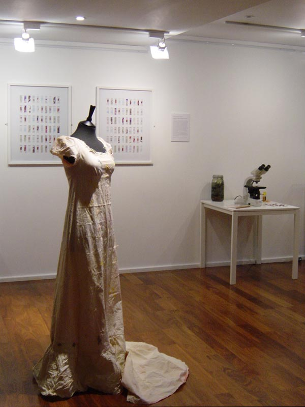 Gallery setting with two charts on the wall. In front, on a mannequin, is a white cotton dress, to the right is table with microscope and other equipment.
