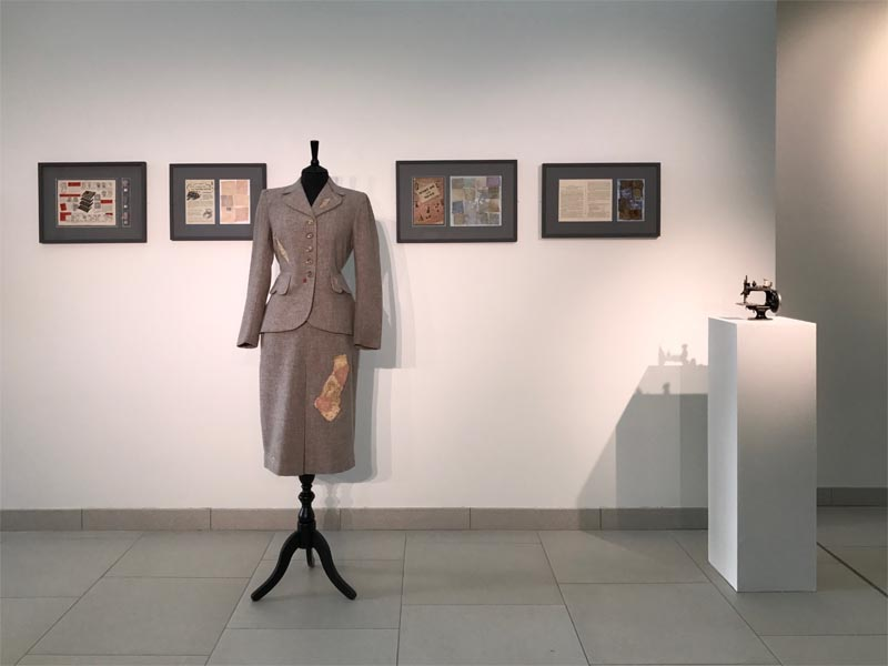 Gallery setting with four pictures on the wall. In front, on a mannequin, is a vintage wartime woman's suit, to the right is a small sewing machine on a table.