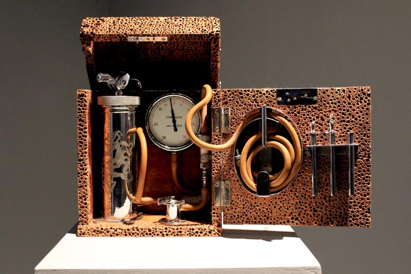 Equipment comprising tubes connected to a dial gauge, a chromed cylinder and other chromed parts. The whole apparatus is contained in a box made from a brown aerated material with hinged lid and front.