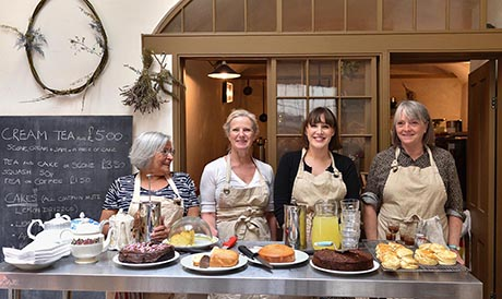 Photo of four women standing behind a table laden with cakes.