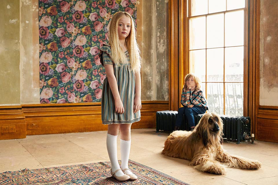 Photo of a little girl standing in a large undecorated room, behind her sits a little boy, at her feet is an Afghan Hound.