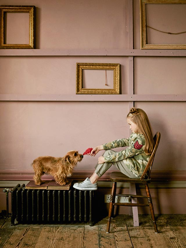 Photo of a little girl sat in a chair and pointing a red water pistol at a small dog.
