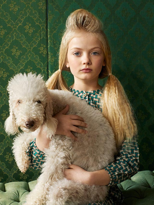 Photo of girl in a green dress holding a white Standard Poodle.