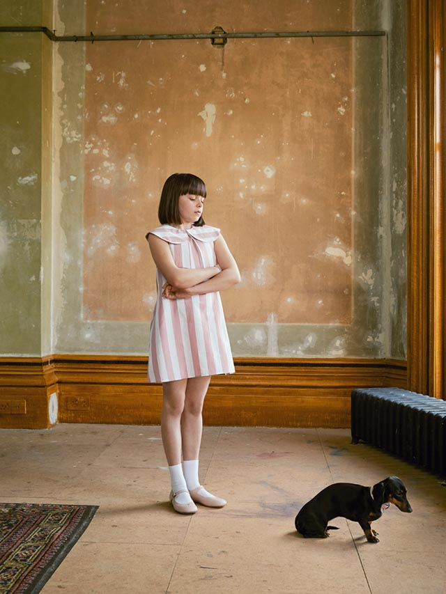 Photo of a girl wearing a white and pink striped dress, standing in an undecorated room and looking down at a small Daschund.