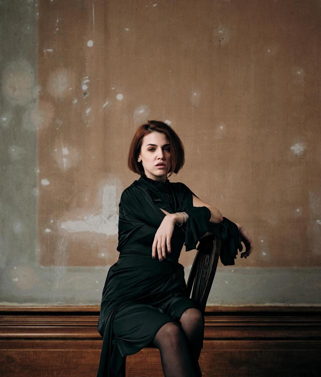 Photo of a young woman wearing a dark, knee-length dress, sitting on a wooden chair, with a bare plaster wall in the background.