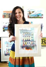 Artist Sarah Jones holding a mounted screen print of The Regency Town House
