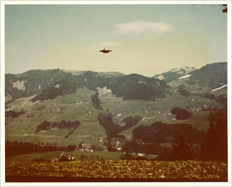 Old colour photo of showing saucer-like object in the sky above mountainous terrain