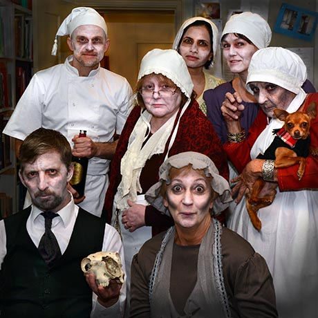 A group of volunteers, faces whitened and in costume for a Hallowe'en event