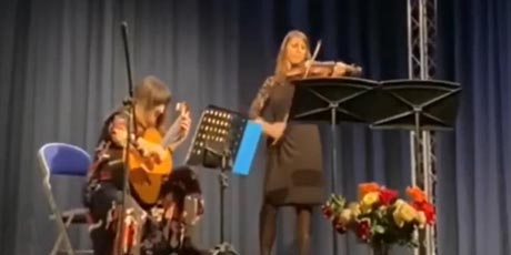 Frame from video of Duo MaLí, showing two women playing guitar and violin on stage.