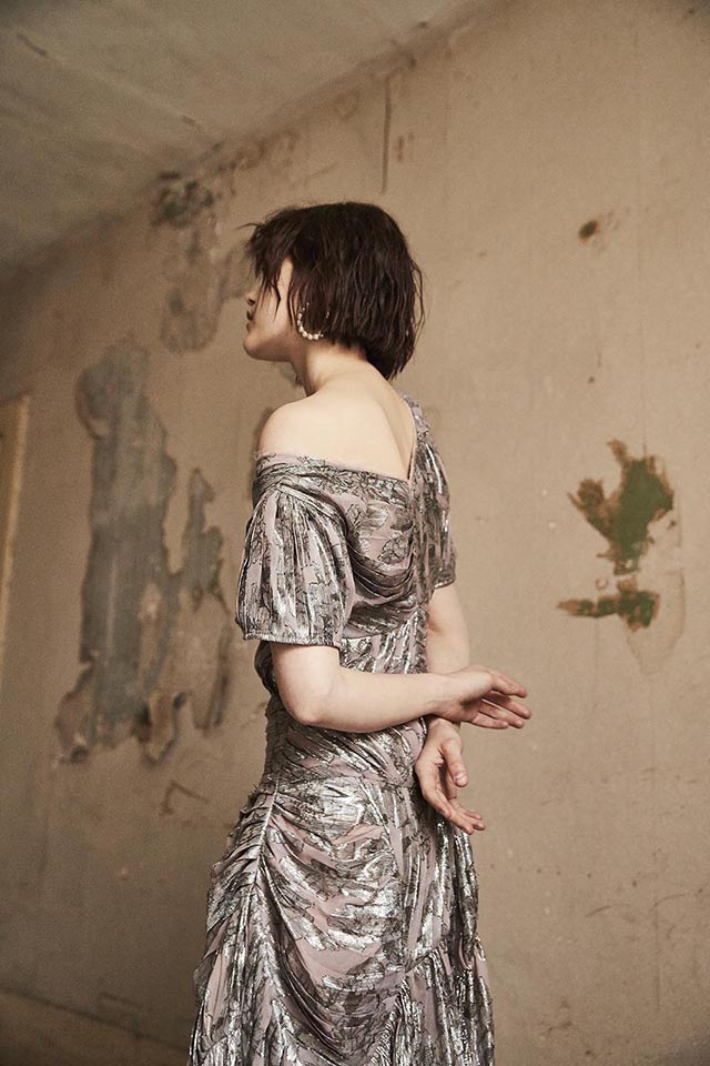 Young woman wearing long silvery dress and standing in a derelict room