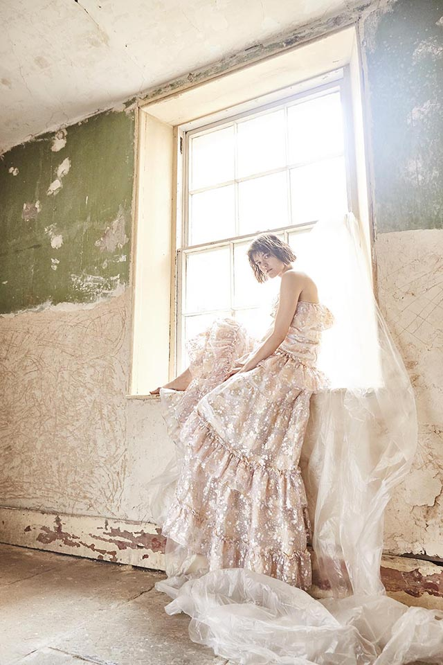 Young woman wearing long white gown, sitting on window ledge in derelict room