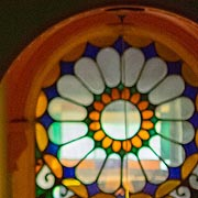 Photo of the stained glass window in the hallway of the Town House, with elements of orange, green, blue and yellow arranged in a circular design.